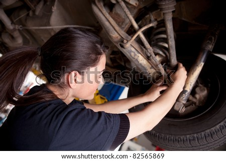 A woman mechanic working on a car, checking a cv boot