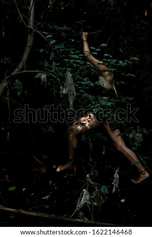 A woman moving through a jungle ストックフォト ©