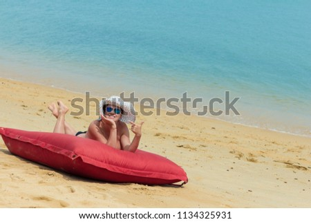 A woman naked in a white hat and sunglasses lies on the beach on a red mattress near the water #1134325931
