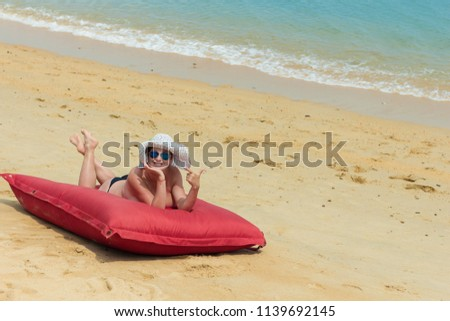 A woman naked in a white hat and sunglasses lies on the beach on a red mattress near the water #1139692145