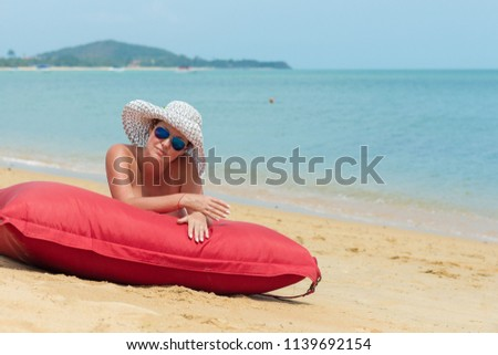 A woman naked in a white hat and sunglasses lies on the beach on a red mattress near the water #1139692154