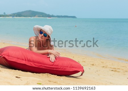 A woman naked in a white hat and sunglasses lies on the beach on a red mattress near the water #1139692163