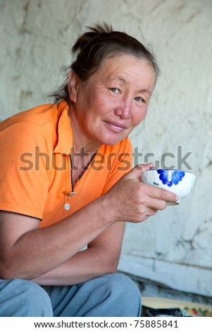 A woman of Asian appearance drinking tea while sitting in her house