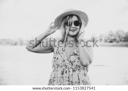 A woman of plus size, American or European appearance walks at park enjoying life. A middle age lady with excess weight, in a stylish dress #1153827541