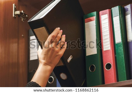 a woman officer pick a binder of document on the row of file folders and paper that nicely management system on the office's shelves and holing it with her hand #1168862116