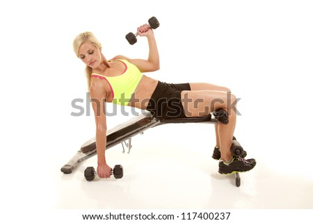 A woman on a bench working out with a weight.