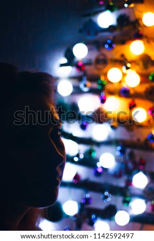 A woman on a Christmas night against a background of a bright Christmas tree made of twigs hanging on the wall and decorated with a garland and toys. #1142592497