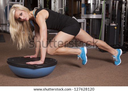 A woman on a half of a ball in plank position bringing in her knee.