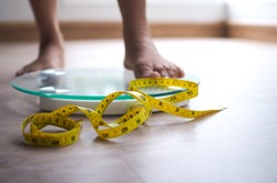 A woman on a scale the yellow tape is in focus. Weight loss diet concept.