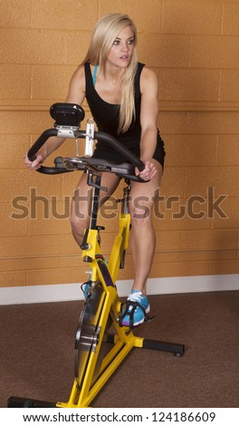 A woman on her bike at the gym working out and getting healthy.