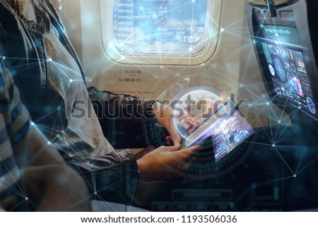 A woman on plane uses the phone thanks to the wi-fi present in flight. He uses holography futuristic. Concept of: travel, vacation, technology, future.