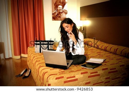 a woman on the bed with notebook in a room hotel