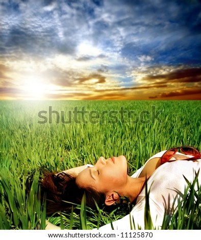 a woman on the grass field and a sunset - stock photo