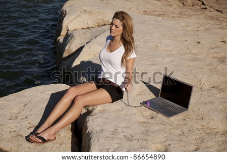 a woman on the rock by the ocean sitting and trying to relax but is still locked to her computer.