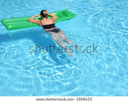 A woman on vacation relaxes in the pool on a summer day