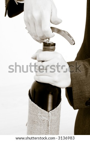 A woman opening a bottle of red wine