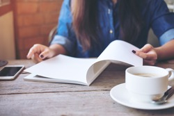 A woman opening and reading a book with coffee cup on wooden table in vintage cafe