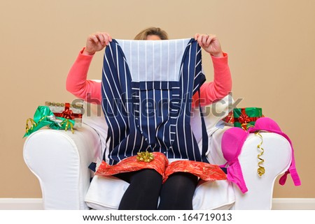A woman opening Christmas presents to discover she got an apron and some underwear.