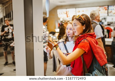 A woman orders food in the touch screen terminal with electronic menu in fast food restaurant