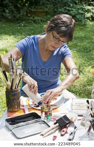 a woman painting a picture in the garden