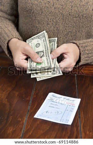 A woman pays her meal bill with cash.