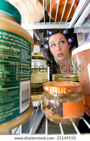a woman peering into an open fridge - domestic series