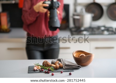 A woman photographer is taking a close-up of autumn fruits and vegetables - mushrooms, garlic, rosemary, and cranberries. On the counter, a wooden bowl. A gas stove and pot in the background.