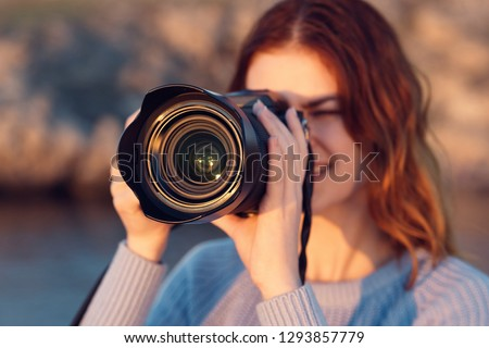 A woman photographer takes pictures of nature