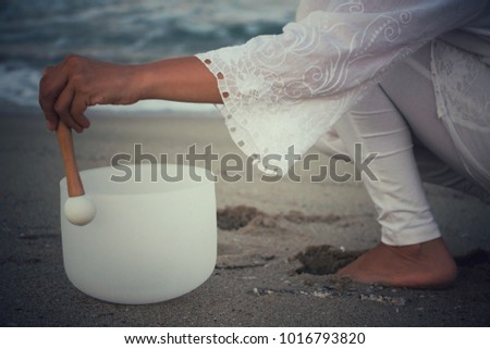 A woman playing a crystal-like singing bowl on the beach.