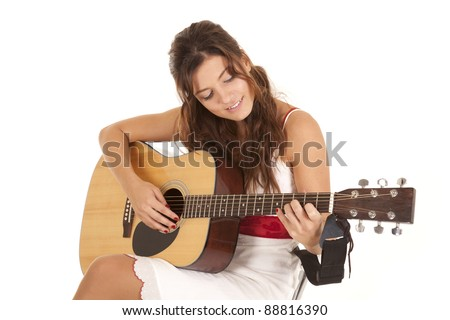 A woman playing her guitar showing off her talent with  a smile on her face.