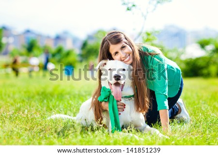 A woman plays with a dog on the grass. Training the dog, the performance of the teams.