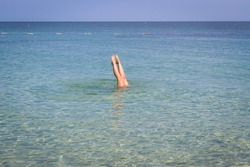 A woman plunging in turquoise sea water. Feet sticking out of the water