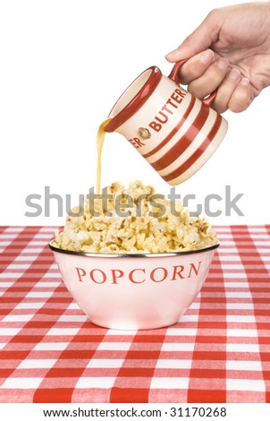 A woman pours hot butter over her bowl of popcorn.