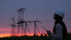A woman power engineer in white helmet inspects power line using data from electrical sensors on tablet. High voltage electrical lines at sunset. Distribution and supply of electricity. clean energy