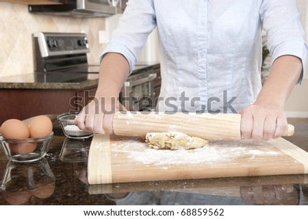 A woman prepares some dough for baking food.