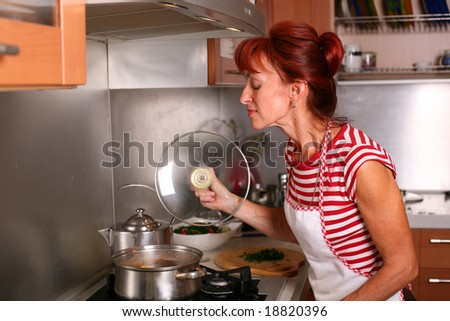 A woman preparing dinner in the kitchen, smells the soup - stock photo