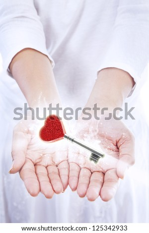 A woman presented a love key with red heart shape on isolated white background - stock photo
