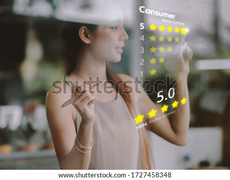A woman presses a button to evaluate services for online shopping on a virtual touch screen .Customer service evaluation concept Foto stock ©