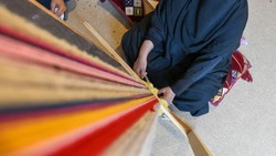 A woman produces traditional Sadu fabric in the Souq Okaz Festival in Taif, Saudi Arabia.