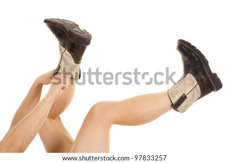 A woman reaching up to pull her cowboy boots on with her hands.