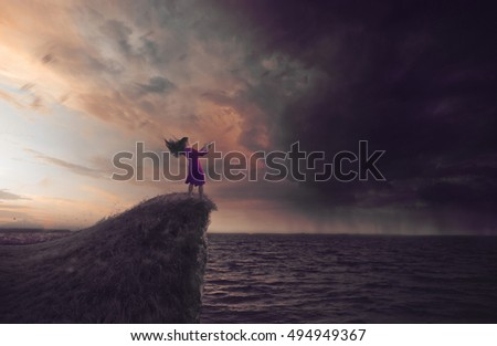 Stock Photo A woman reads a book while the wind blows from an approaching storm