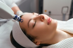 A woman receives laser treatment of the face in a cosmetology clinic, a concept of skin rejuvenation is being developed. laser peeling.