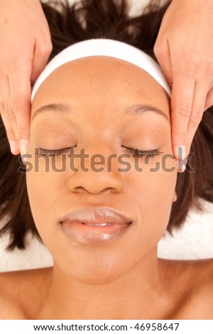 a woman relaxes as her head gets massaged