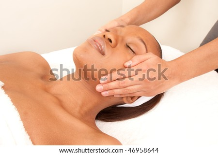 a woman relaxes as she gets a facial massage