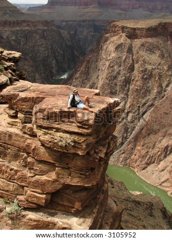 A woman relaxes at plateau point over the Colorado River, Grand Canyon, Arizona