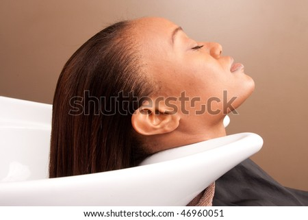 a woman relaxes her head in a sink at a salon