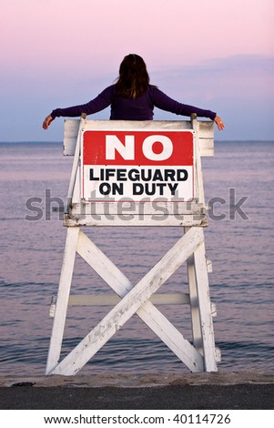 A woman relaxes in a vacant lifeguard chair and watches the beautiful sunset.