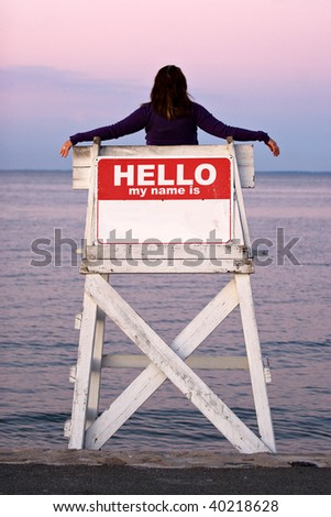 A woman relaxes in a vacant lifeguard chair where the sign on the back reads HELLO MY NAME IS.