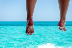A woman relaxes with her feet hanging off the side of a boat while traveling over the blue waters near Caye Caulker, Belize, Central America.