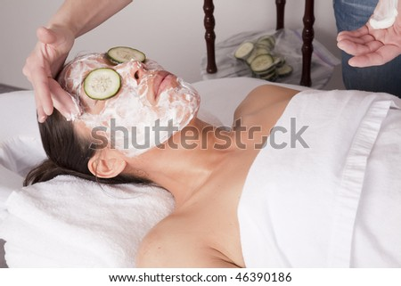 A woman relaxing and getting cream put on her face after a massage.